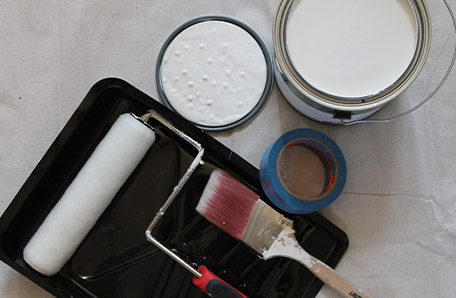 Behr Paint roller, paint brush, painter's tape, and a gallon of Behr paint