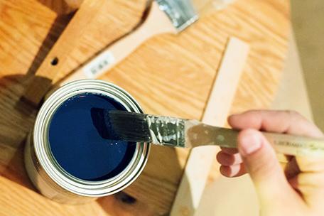 Brocha para molduras sumergida en un bote de un cuarto de galón de pintura BEHR PREMIUM PLUS ULTRA