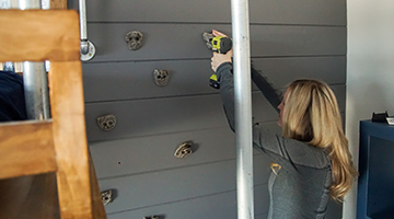 Installing rock climbing holds on the shiplap wall