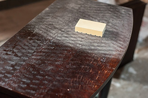 Sanding the table top with a sanding block
