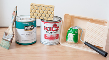 Gallon cans of BEHR PREMIUM PLUS paint and KILZ ORIGINAL primer