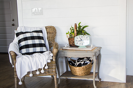Wicker chair and site table in front of the finished shiplap wall