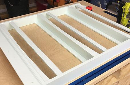 Biblioteca pintada sobre una mesa de trabajo con los rieles para los estantes instalados