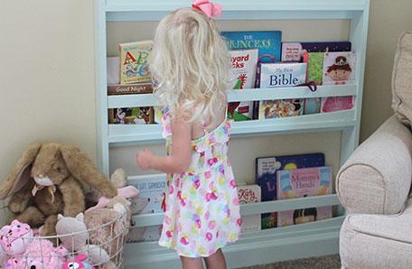 Niña pequeña con un vestido de lunares tomando un libro de la biblioteca