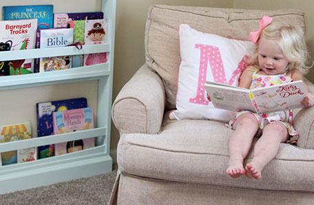 Niña pequeña sentada en una silla, leyendo un libro