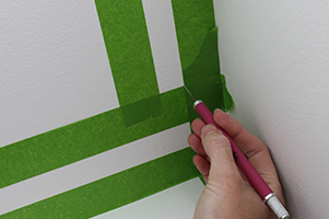 Create accent wall frame using tape and craft knife