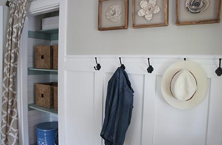 Clóset recién terminado junto a una pared revestida en madera con colgantes para abrigos