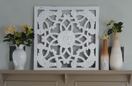 Una malla de metal con diseño de estampa y floreros sobre la repisa de la chimenea