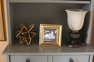 The hutch is a great place to display family photos and an antique lamp