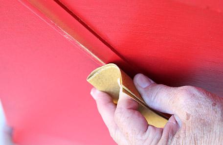 Use una lija de grano fino para lijar la pintura y lograr una apariencia desgastada