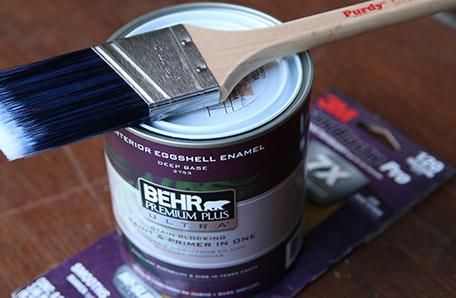 Una brocha limpia, un cuarto de pintura Behr y un papel de lija