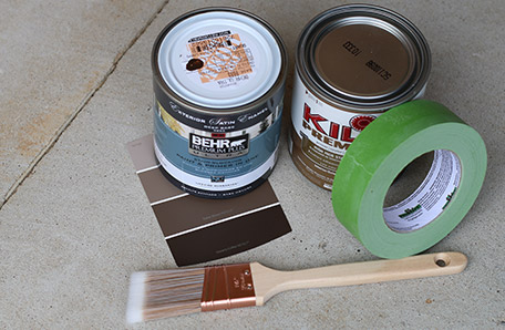 Paint brush, Behr color chips, painter's tape, and a quart each of paint and primer