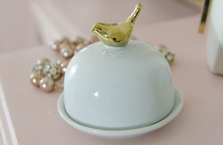 Close up on vanity with ceramic bird jewelry holder