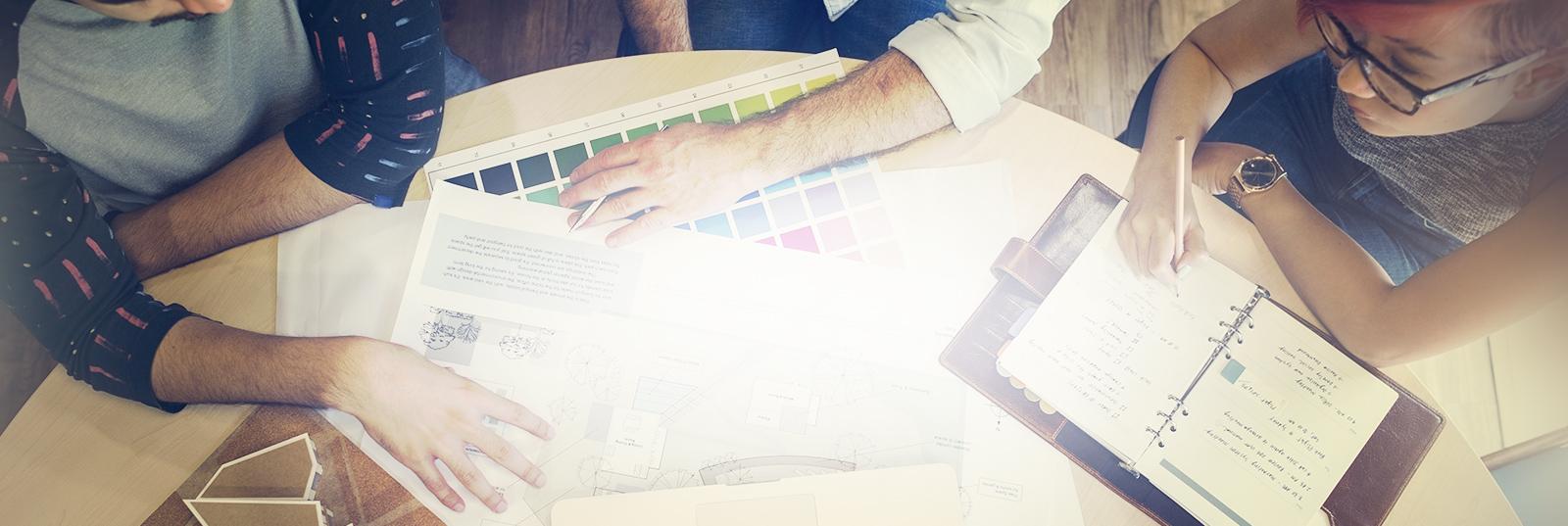 Personas sentadas frente a un escritorio consultando una laptop y eligiendo colores
