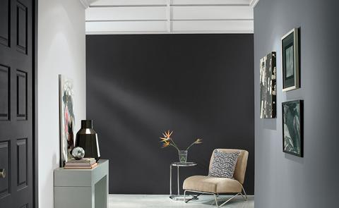Habitación en color gris con pared oscura y sillón y marcos sobre la pared.
