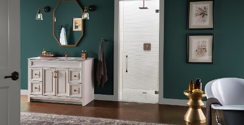 Bold and dramatic styled bathroom with teal green walls, white trim, and white vanity.