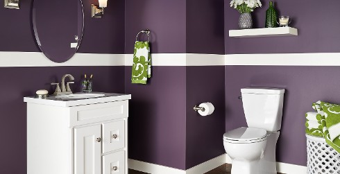 Bold and dramatic styled bathroom with deep purple walls, white trim, white vanity, and oval mirror.