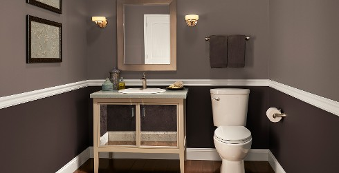 Earthy themed bathroom with deep brown and brown split walls, white trim, mirrored vanity, and square mirror.