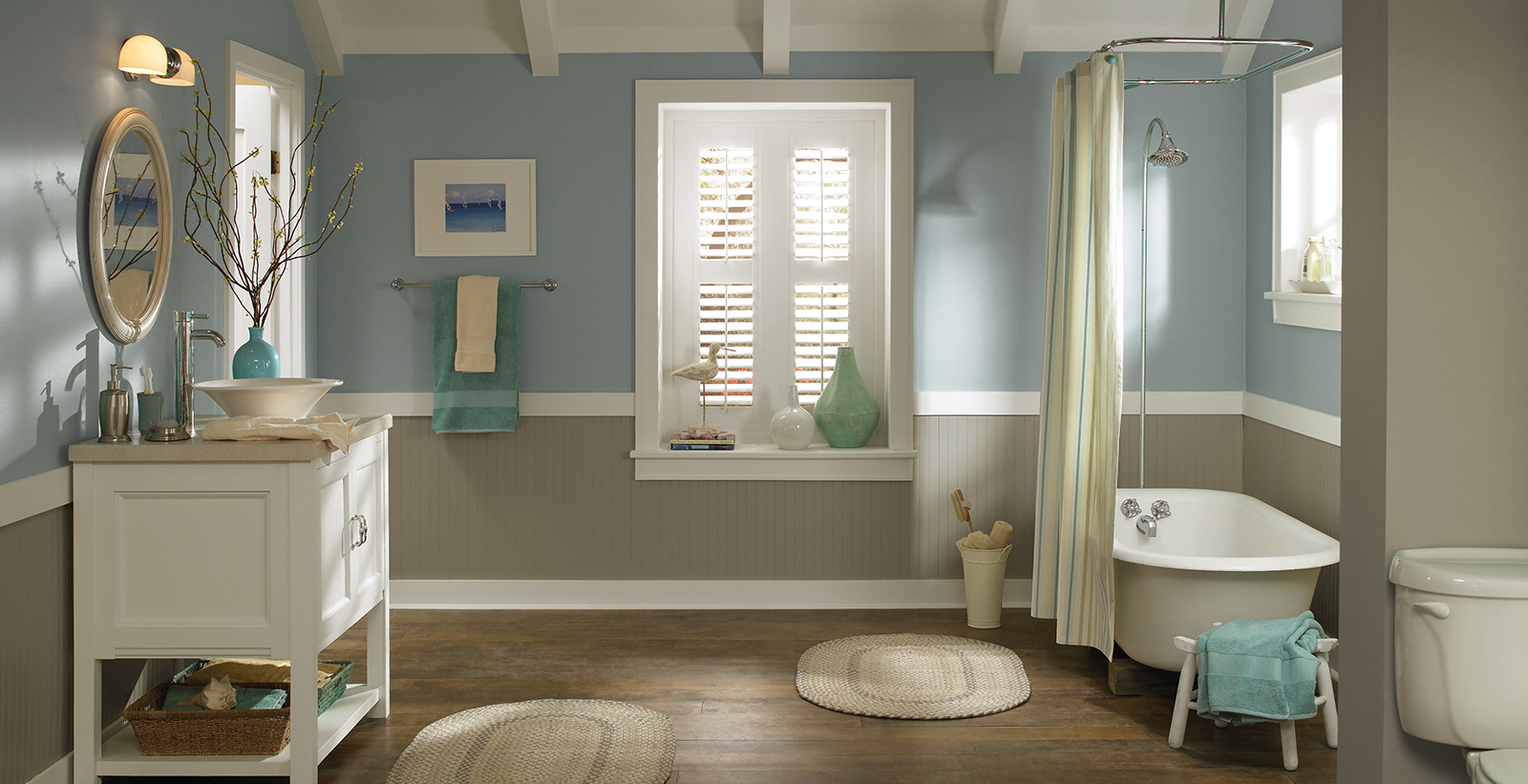 Casual styled bathroom with tan and light blue split walls, white trim, white vanity, and oval mirror.