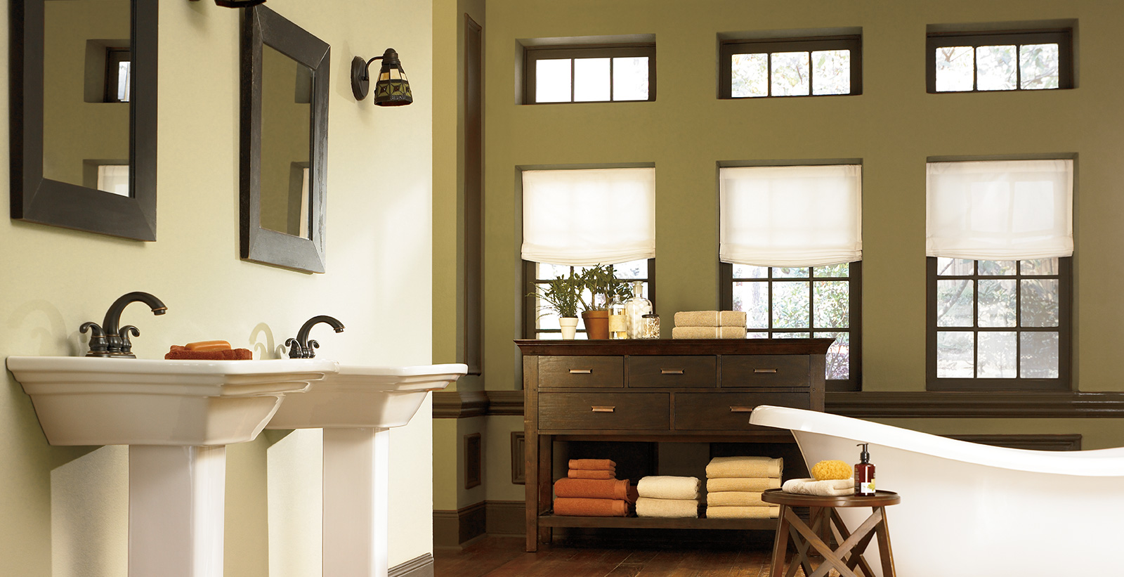 Casual styled bathroom with tan and green walls, brown trim, brown vanity, dual sinks, and square mirrors.