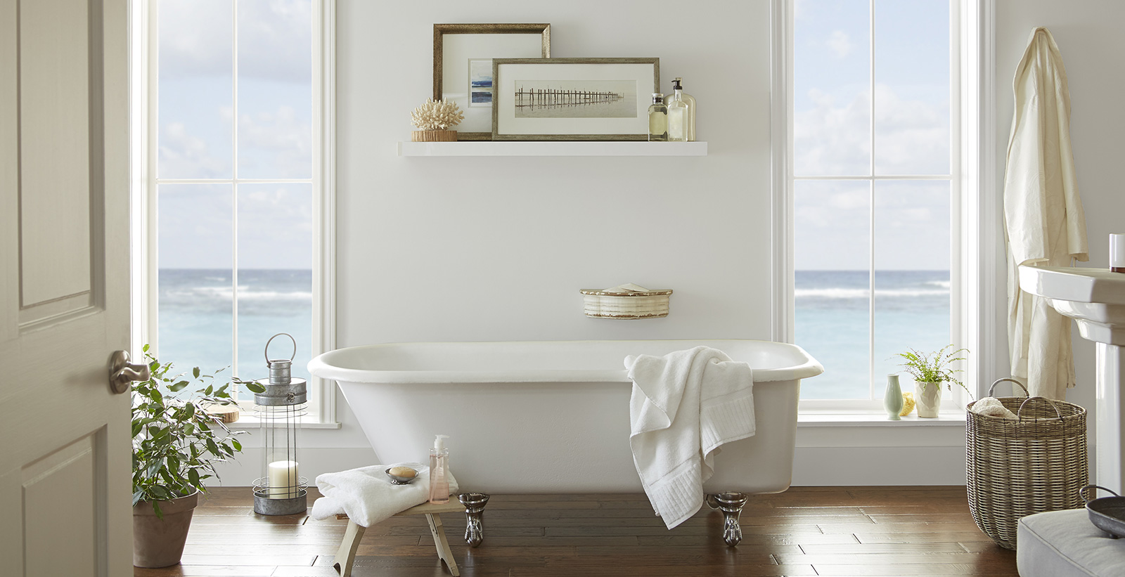 Casual styled bathroom with white walls, gray door, white trim, and seaside window view.