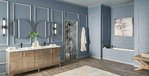 Classic styled bathroom with charcoal blue walls, gray trim, with dual vanities, and oval mirrors.