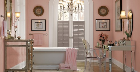 Classic styled, glamour bathroom with pink walls, white trim, brown shutters, vintage vanity and mirror.