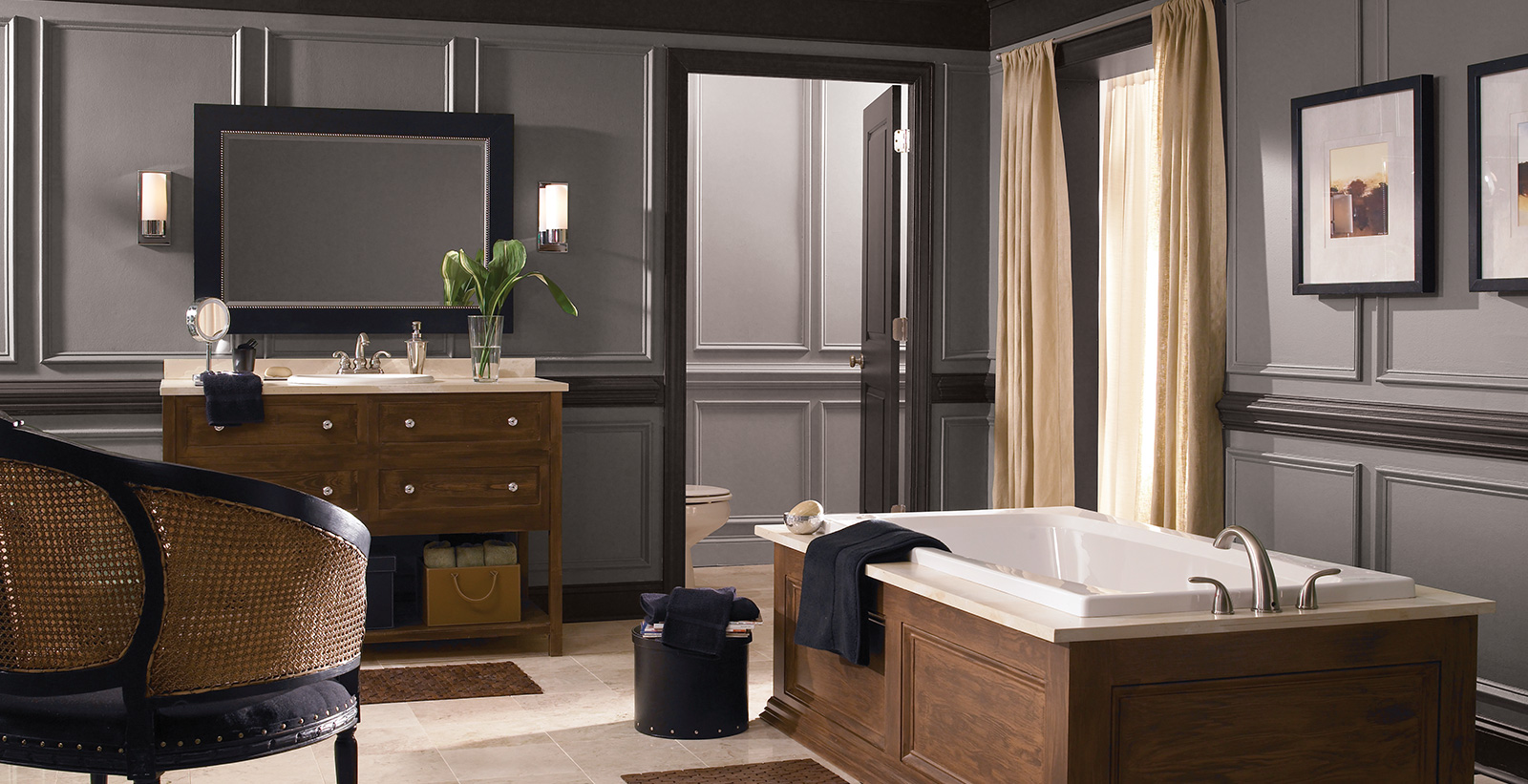 Classic styled bathroom with gray walls, brown trim, wooden vanity and rectangular mirror.