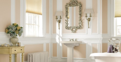 Inviting roman themed bathroom with orange walls, white trim, white sink, and rectangular mirror.
