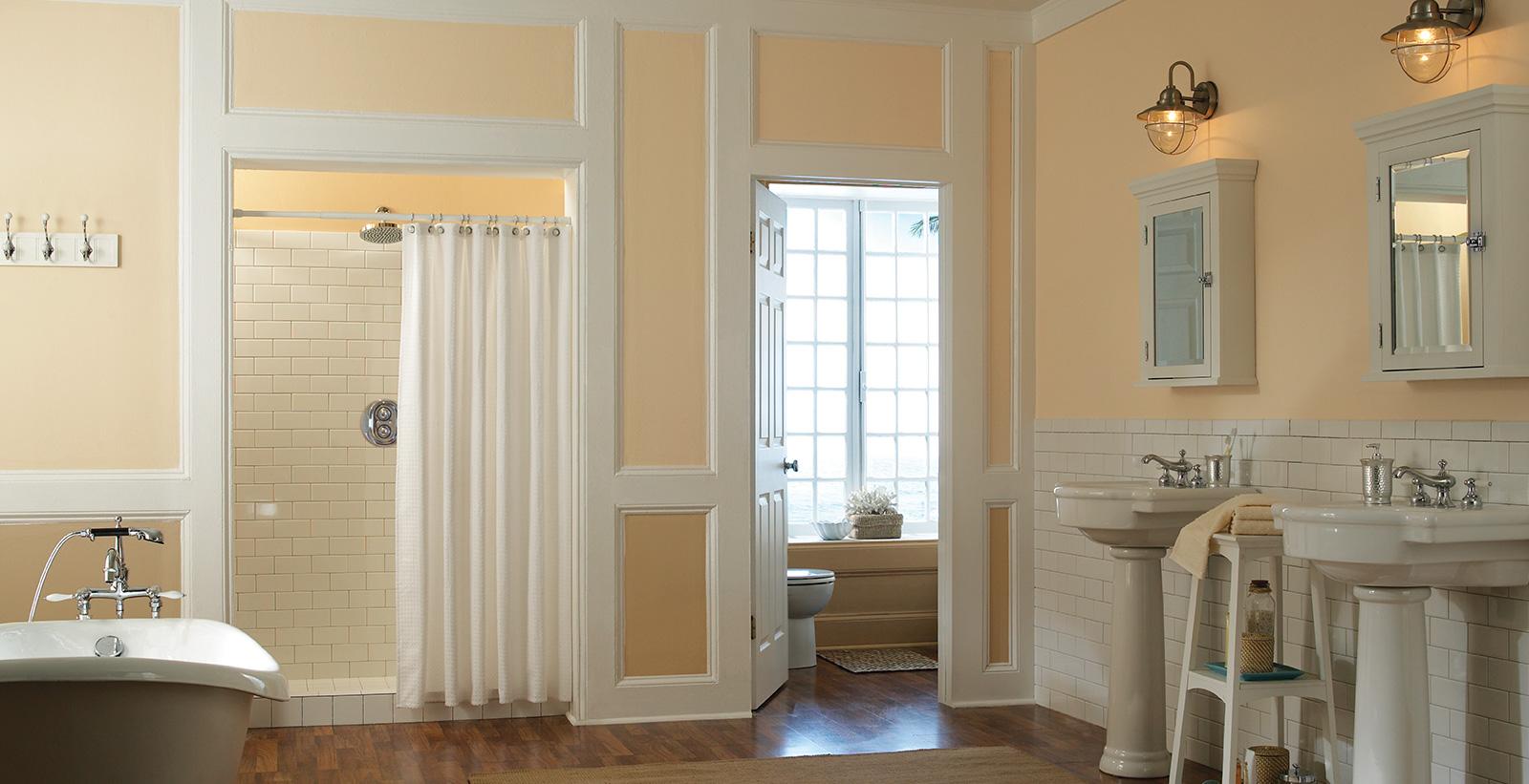 Baño para parejas con paredes anaranjadas y molduras blancas.
