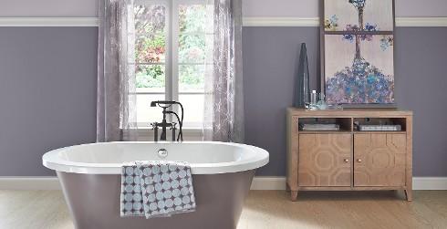 Cuarto de baño con paredes moradas y molduras blancas para lograr un estilo de relajación y calma.