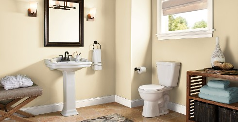 Warm styled bathroom with yellow walls and white trim.