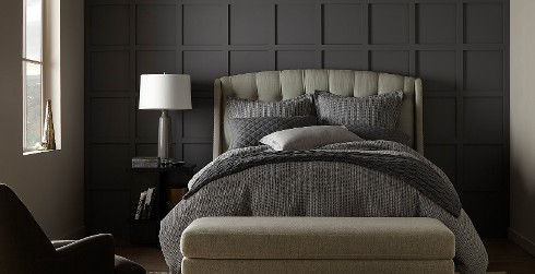 Urban styled bedroom with charcoal gray on accent wall, light gray on main walls, and gray tufted headboard