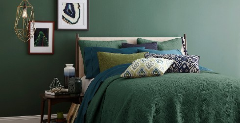Bold bedroom with forest green on walls, white on trim, and dark green and blue bedding