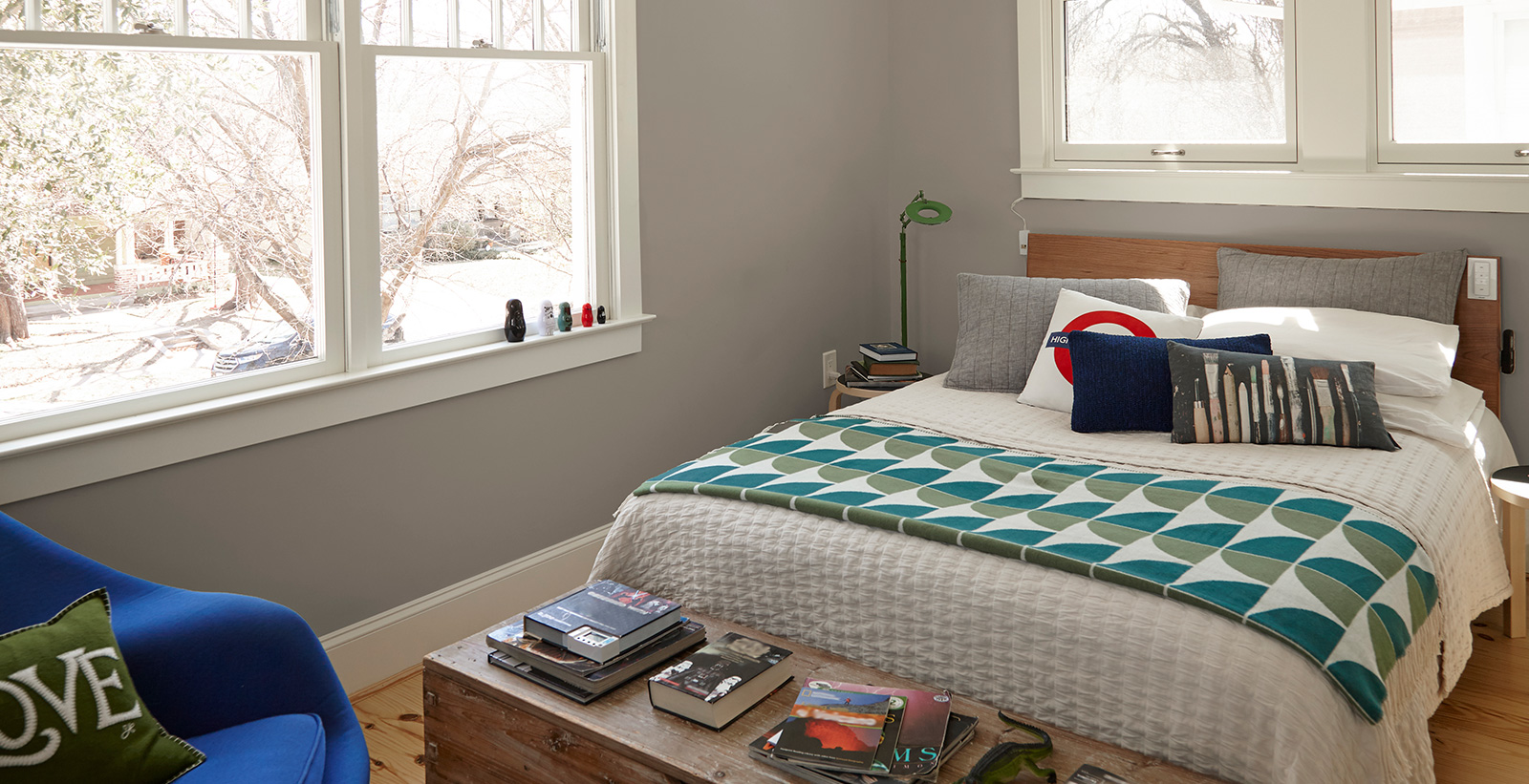 Casual bedroom with light gray on walls, white on trim, and cobalt blue upholstered chair