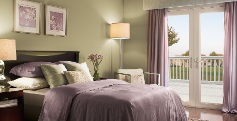 Classic bedroom with sage green on walls, white on trim, and lilac bedding