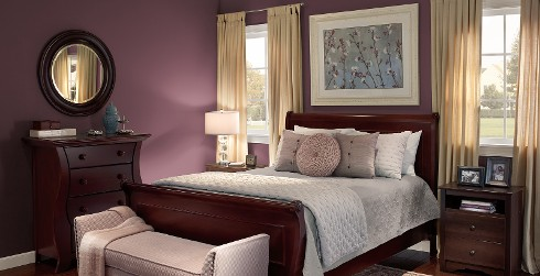 Classic luxury bedroom with purple on walls, white on trim, and dark wood bed frame and dressers