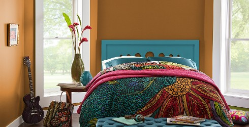 Boho inspired bedroom with orange on walls, white on trim and multi-colored floral bedding with turquoise headboard