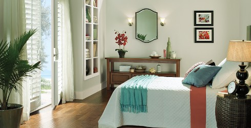 Eclectic bedroom with greenish white on walls, white trim, and wood flooring