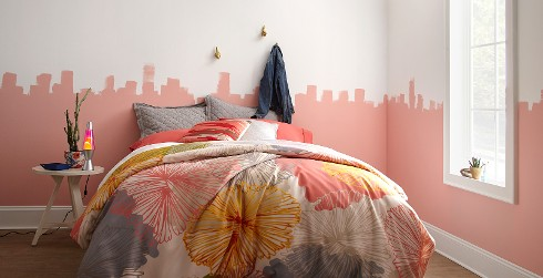 Artistic bedroom with white on top half of wall, pink on bottom half, white on trim and multi-colored bedding