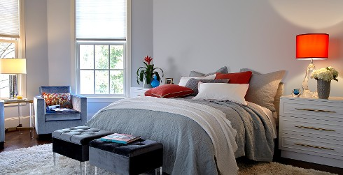 Modern bedroom with light gray on walls, white trim and dressers, and white shag rug