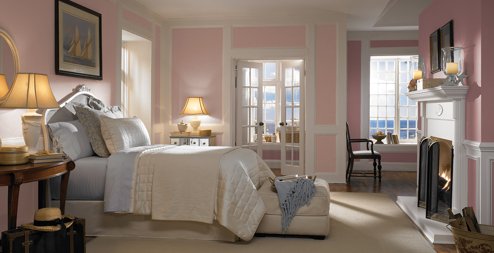 Coastal styled bedroom with light pink on main walls, mauve pink on accent walls, and white on trim and fireplace mantel