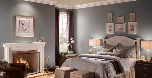 Classic bedroom with grayish blue on walls, white on trim and fireplace, and light tan on ceiling
