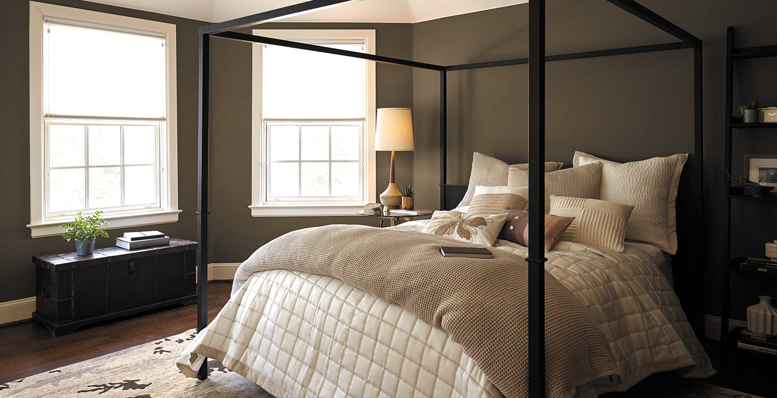 Contemporary bedroom with muted brown on walls, white on trim and ceiling, and neutral bedding on metal 4 poster bed