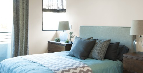 Casual bedroom with white on walls, blue bedding, and dark wood dressers