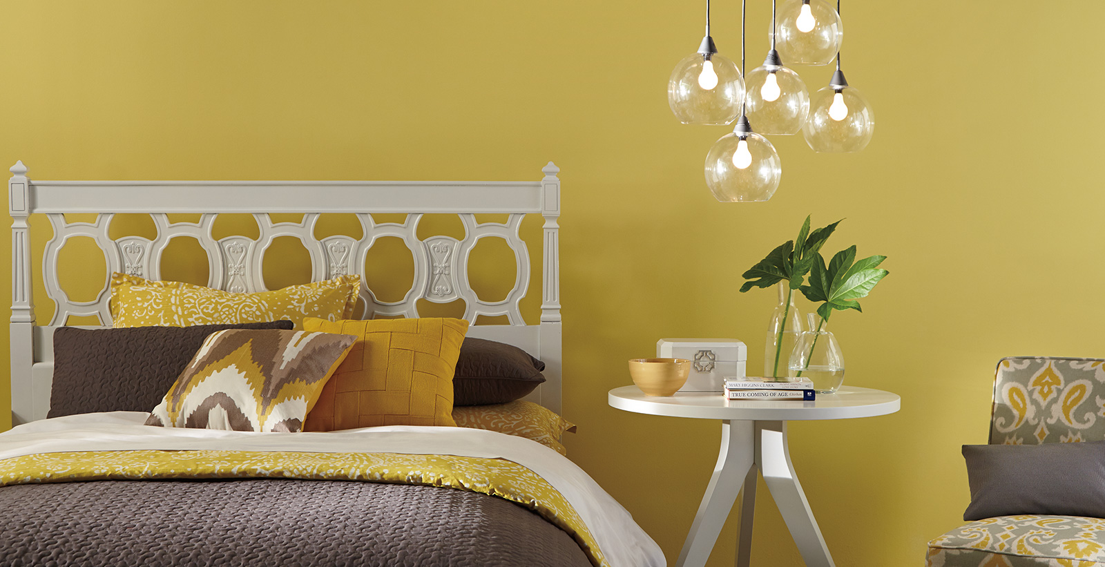 Bright bedroom with yellow on walls, white geometric cutout headboard and hanging globe lights