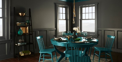 Moody farmhouse dining area with dark moss green on walls, dark olive brown on wainscotting and bright teal pedestal dining table and chairs.