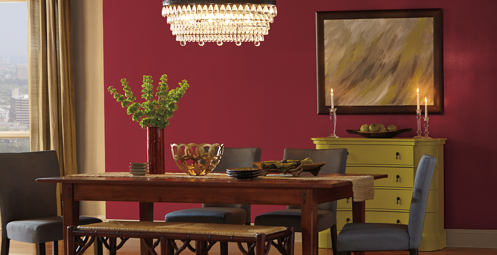 Dining room with pure red walls and off white trim, rustic furniture, eclectically styled.