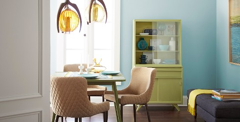 Sunny dining space with teal blue walls, bright green dining hutch and table.