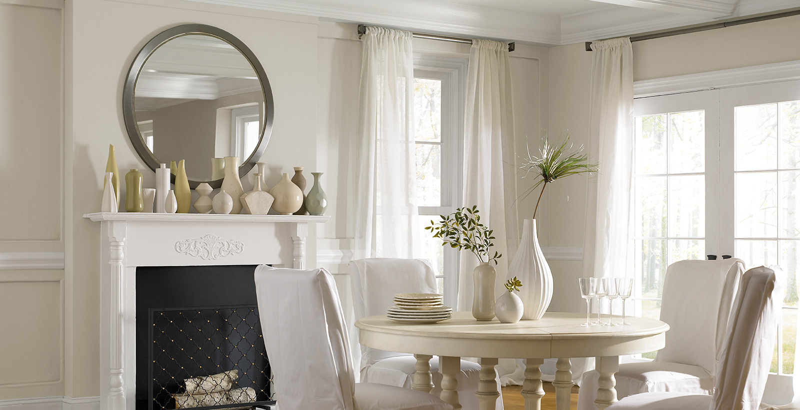Relaxed style of dining room with off-white walls and white trim, with white stone fireplace and floor to ceiling windows.